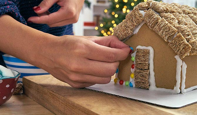 Decorating beach gingerbread house with wheat cereal and candy
