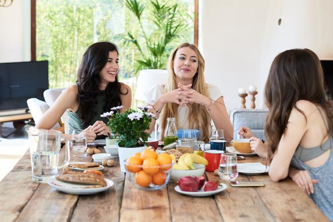 Cheerful girlfriends talking while having healthy breakfast in living room.