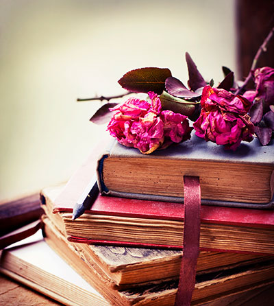 stack of old books with pink roses on top