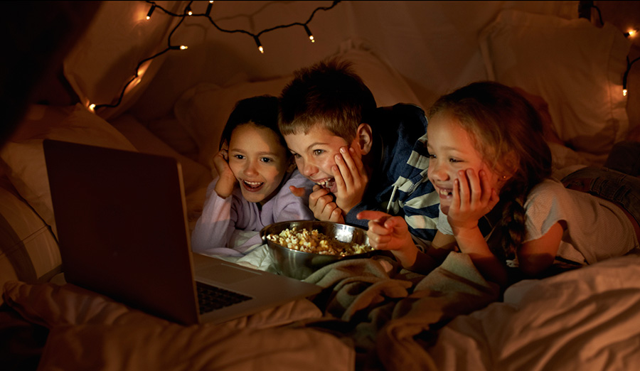 Children in a tent watching a movie on a laptop