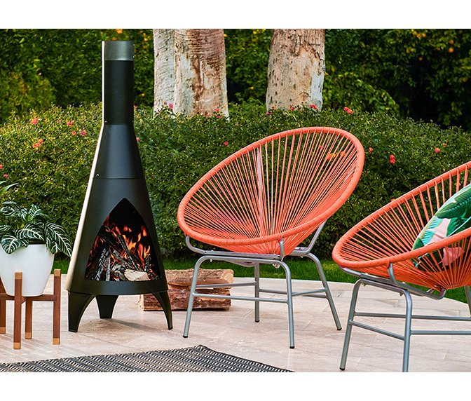 A Mid Century Modern Outdoor Setting With Red Acapulco Chairs Retro Fireplace