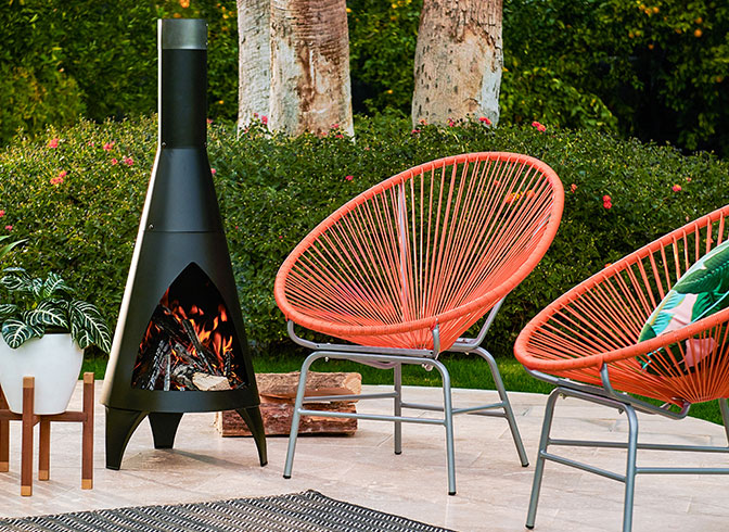 A Mid Century Modern Outdoor Setting With Red Acapulco Chairs, A Retro  Outdoor Fireplace