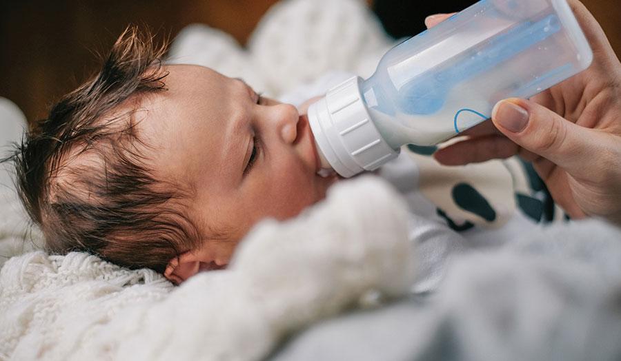 Mom bottle feeding infant on a soft blankets