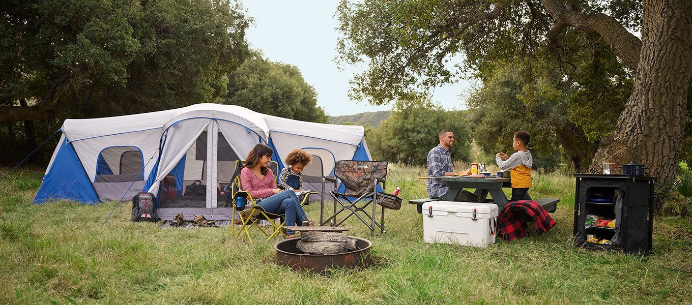 family sitting around their campsite, father and son working on dinner, blue dome family tent in the background