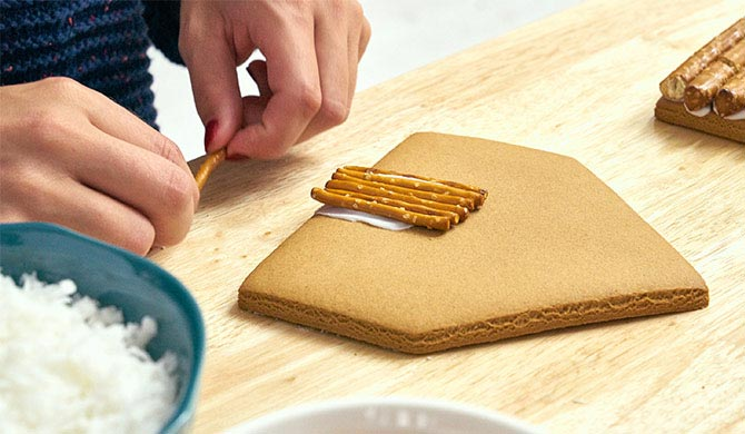 Adding a pretzel door to the gingerbread house log cabin