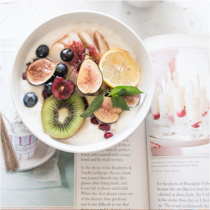 A white bowl filled with oatmeal topped with fresh fruit and an open book with healthy recipes inside.