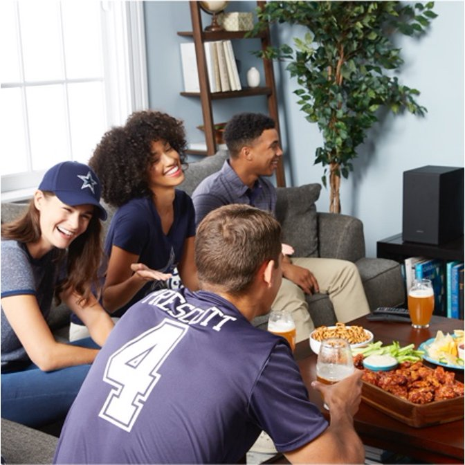 A group of friends sitting on a gray sectional, eating snacks and getting ready to watch the football game