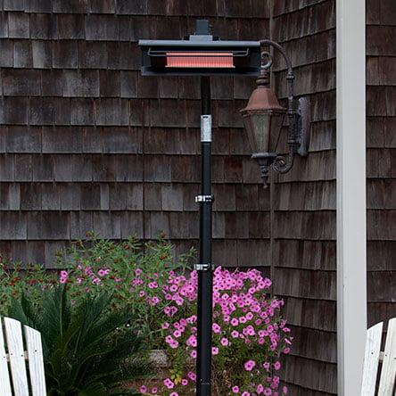A black electric patio heater in a backyard. Links to the best electric patio heaters on Walmart.com.