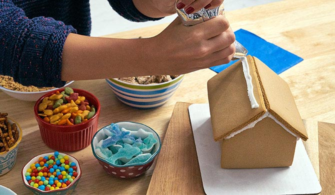 Adding frosting to roof of beachy gingerbread house