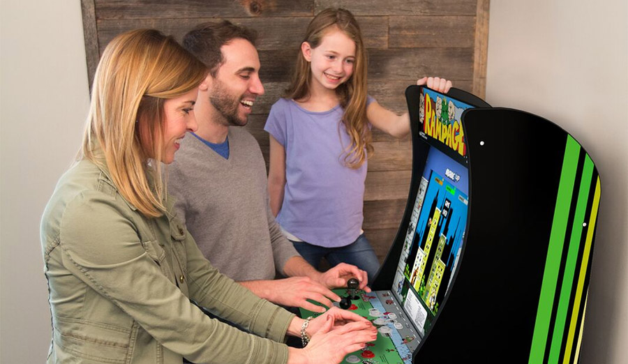 A family enjoys the Arcade1Up cabinet featuring Midway classics like Rampage.