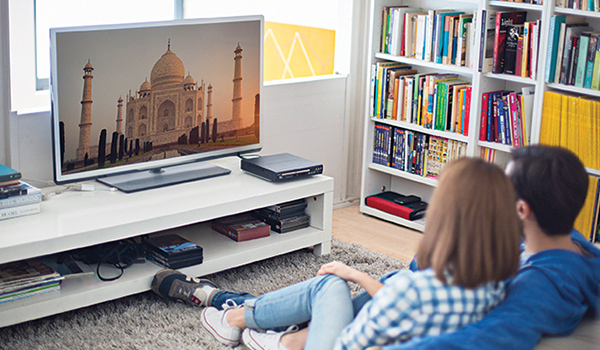 TV buying guide - couple sitting on a couch watching a movie on their HD TV