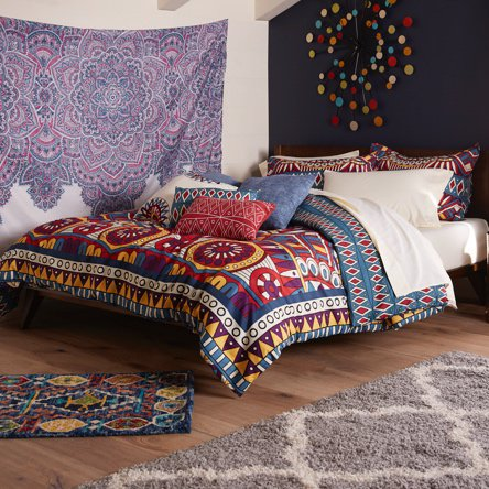 A bohemian style bedroom with a dark accent wall, wall tapestry and boho style mixed and matched bedding.