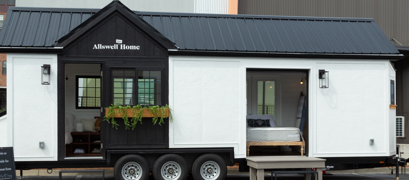 The exterior of the Allswell Tiny Home with its pitched roof and little garden planters. Links to a blog post about what is the Allswell Tiny Home.