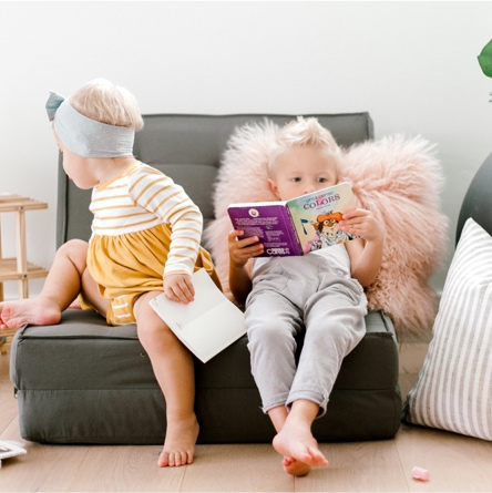 Two toddlers sitting on a Your Zone flip chair with a faux fur pillow and a shoe shelf bookshelf.