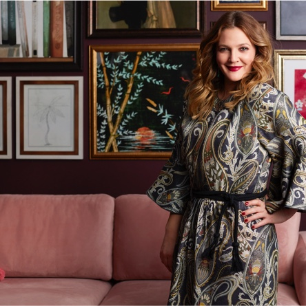 Drew Barrymore smiling at the camera in front of a gallery wall of sophisticated artwork. Links to a blog post about how to recreate three gallery walls curated by Drew Barrymore.