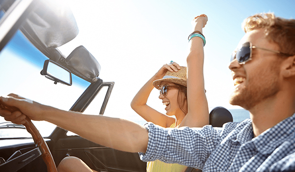 couple driving in convertible in summer
