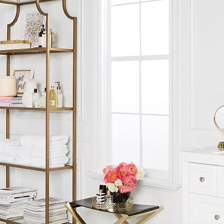 404548e9eb6 A set of gold shelves in a glam bath with towels hung on the wall and