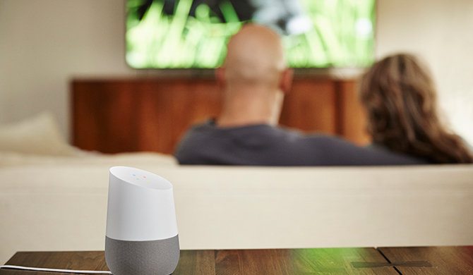 Google Home Sitting On A Table In The Foreground With Couple Sitting On The  Couch Watching