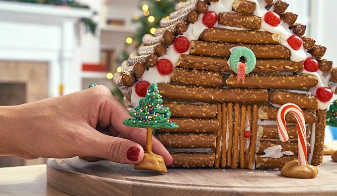Adding green chocolate pretzel tree to gingerbread house log cabin