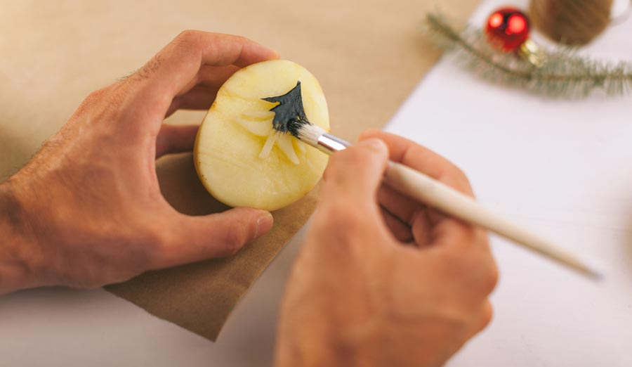 Hands painting a potato stamp with fabric paint
