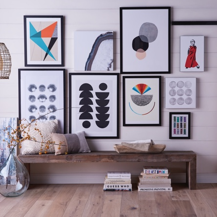 A modern gallery wall with a portrait of Twiggy and abstract prints above a rustic entryway bench. Introduces a blog post about how to style a unique gallery wall.
