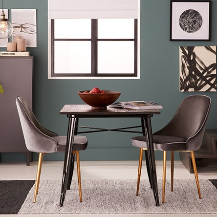 A modern dining room with velvet accent dining chairs and storage.