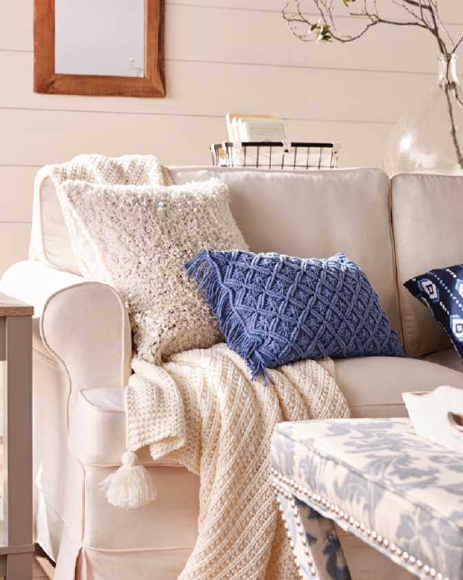 A farmhouse living room with a beige farmhouse style sofa, woven decorative pillows and rustic decor.