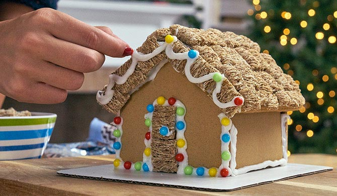 Decorating gingerbread house with wheat cereal and candy