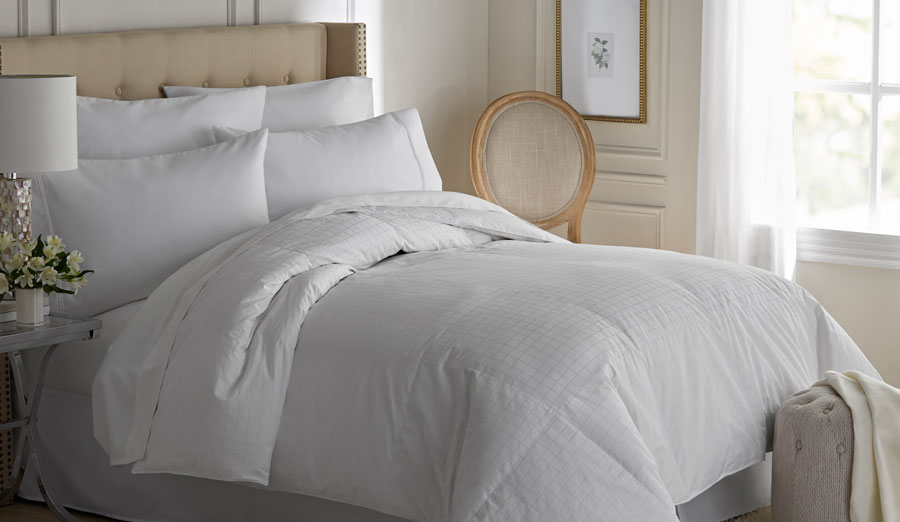 Bed with upholstered headboard in bedroom with white bedding, comforter and pillows