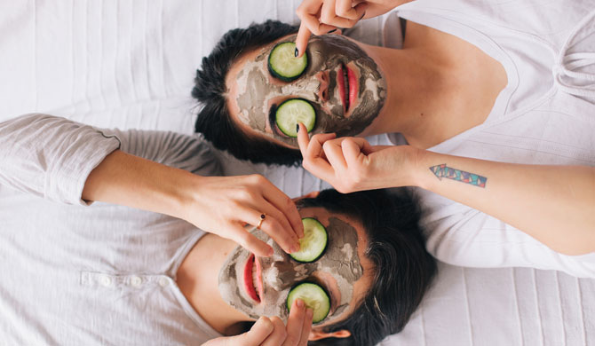 Two women wearing clay face masks