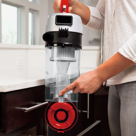 A woman opening the canister of a vacuum to clean it out before another use. Start a blog post about how to care for your vacuum to prolong its life and improve your vacuums performance