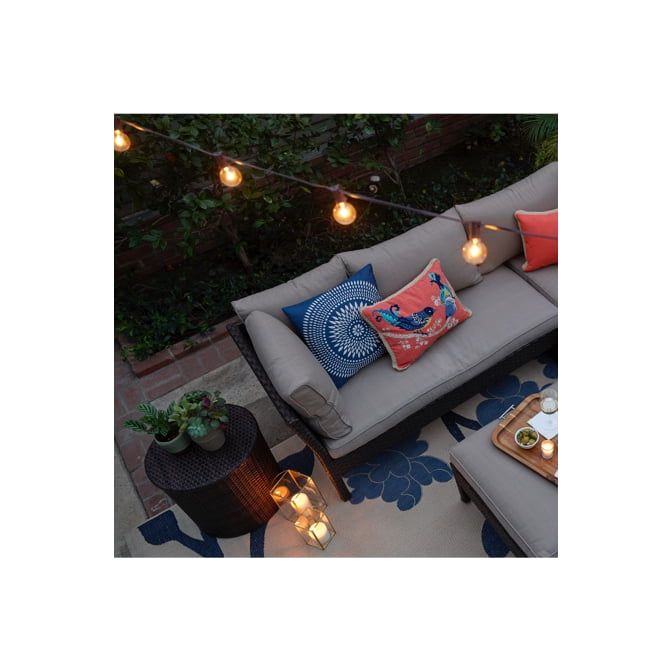 An outdoor living area with string lights glowing above showing the power of outdoor lighting for your outdoor living space.
