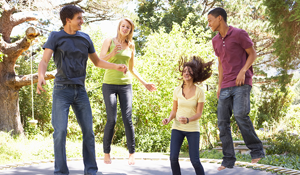 4 young people jumping on an outdoor tampline