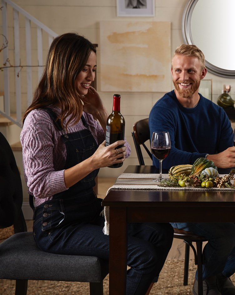A hostess with a bottle of wine ready to serve friends at a farmhouse table with a cheese plate and shiplap walls in the background.