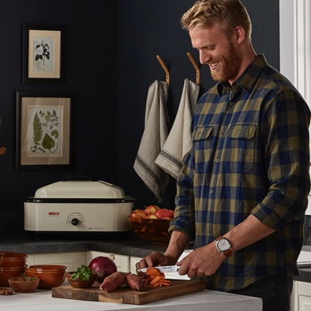 A bearded man who is hosting a holiday dinner party cutting sweet potatoes on a wooden cutting board with a roaster in the background. Starts a blog post about kitchen hacks that make holiday meals easy.