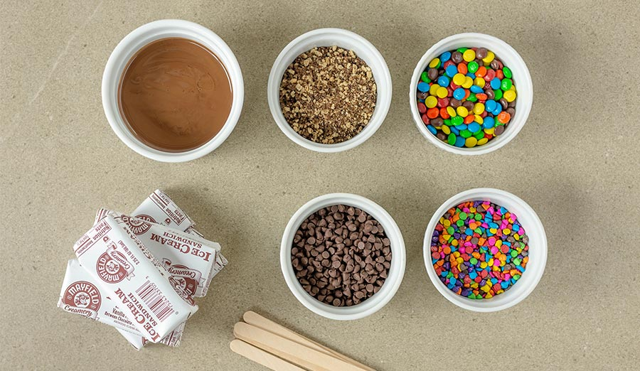 Supplies for Ice Cream Sandwich pop: ice cream sandwiches, craft sticks, Magic Shell, and toppings like sprinkles and nuts