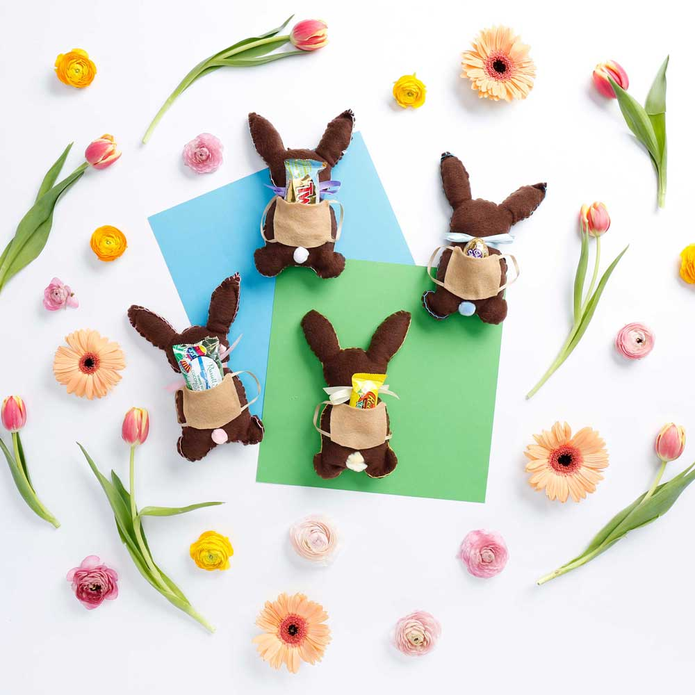 4 bunnies with candy in their backpacks surrounded by spring flowers