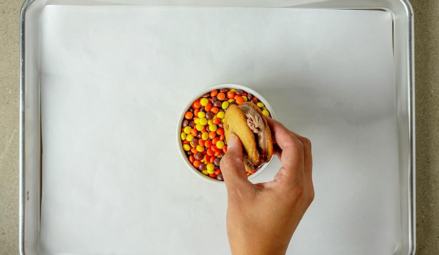 Dipping ice cream sandwich cookie into Reese's Pieces Minis