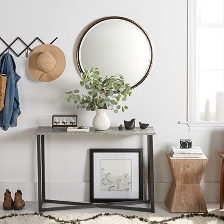 A Scandinavian style entryway with a circular wall mirror, black minimalist iron console table, criss cross wall hooks and wooden side table.