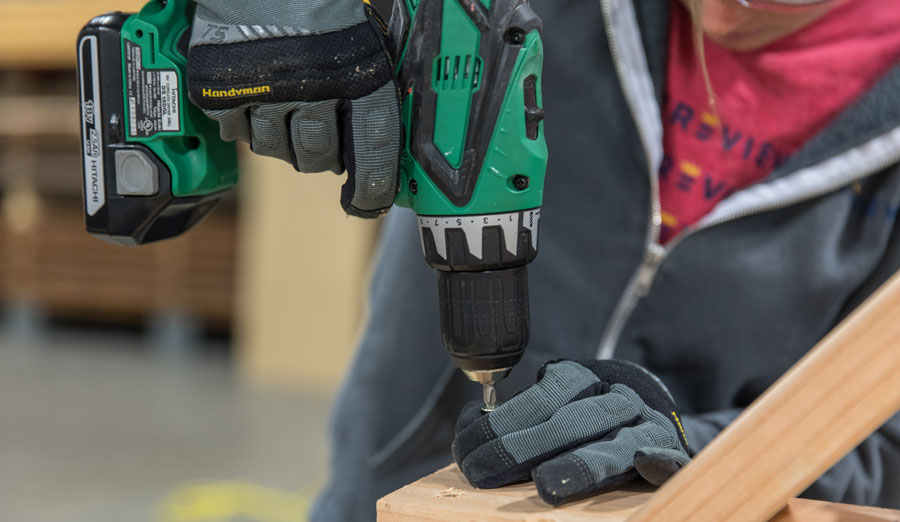 Close up of woman using Hitachi cordless drill to drive screw into piece of wood