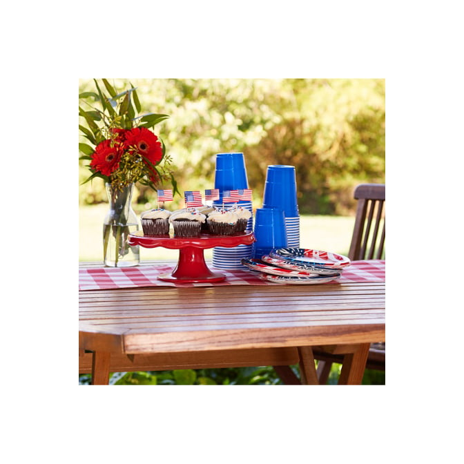 A 4th of July table with gingham runner, flowers, and 4th of July cupcakes.
