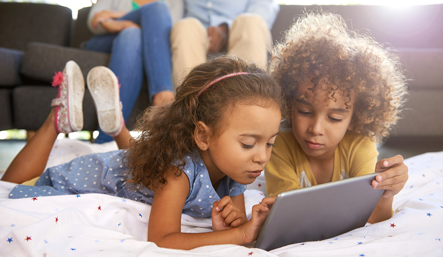 Two young girls playing on a tablet