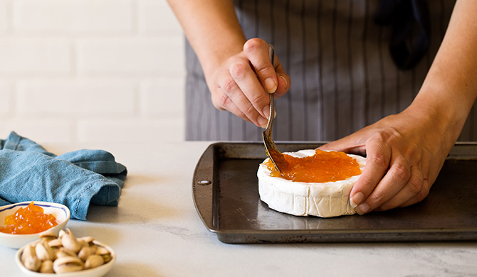 Spreading jam on brie, on a sheet pan