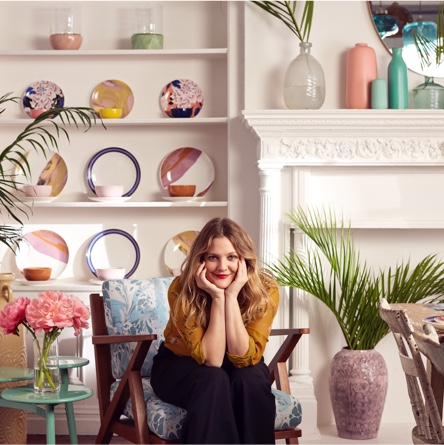 Drew Barrymore sitting in a mid-century modern style chair smiling at the camera with colorful dishware and palm trees in the background. Links to a blog post about how easy it is to style Drew Barrymore Flower Home.