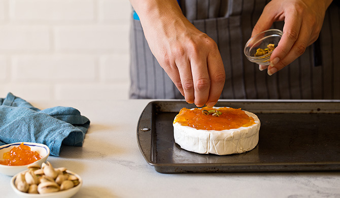 Adding pistachios to brie spread with apricot jam, on a sheet pan