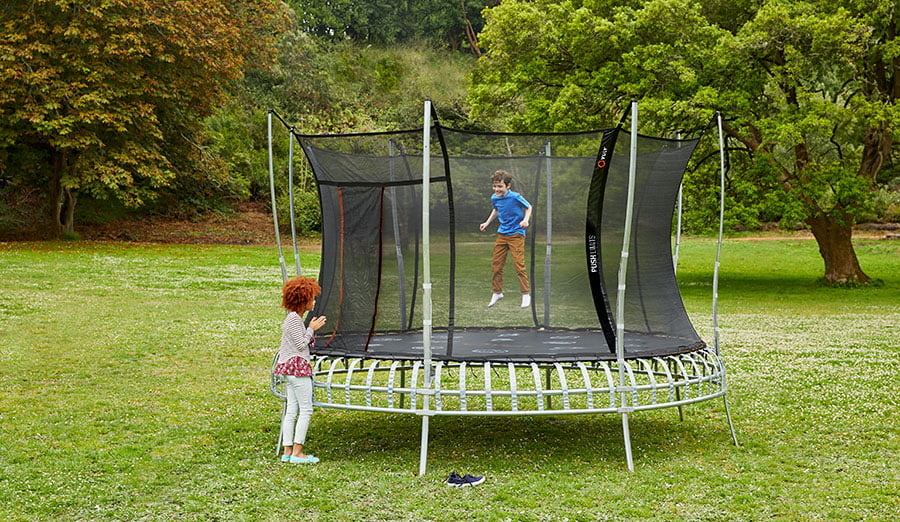 Two children playing out in an open space on a trampoline.